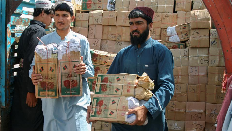 Labourers unload boxes of pomegranates from Afghanistan, from a truck at the 'Friendship Gate' crossing point, in the Pakistan-Afghanistan border town of Chaman, Pakistan on September 7, 2021.
