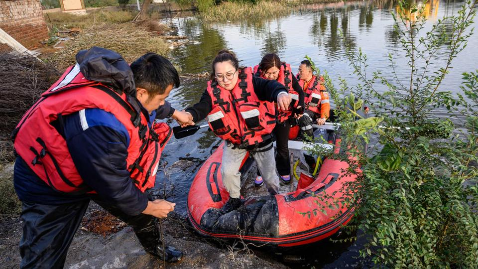 Rescuers evacuate residents in a flooded area after heavy rainfalls in Jiexiu, in Jinzhong city, China's northern Shanxi province on October 10, 2021.