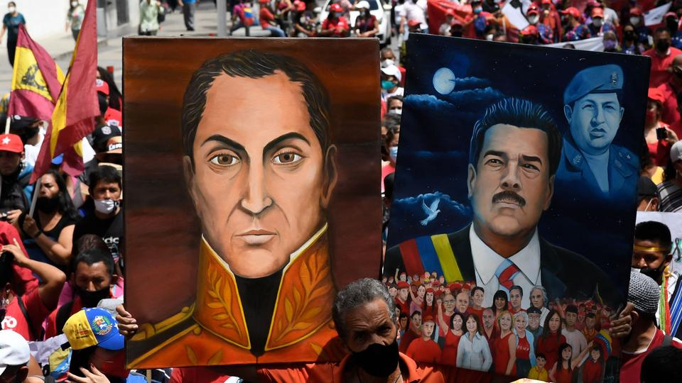 A supporter of Venezuela's President Nicolas Maduro, holds portraits of him (R) and Venezuela's national heroe Simon Bolivar, during a march to commemorate the day of Indigenous Resistance, in Caracas on October 12, 2021.