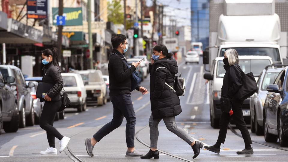 People cross a street in Melbourne on October 11, 2021 during a lockdown against Covid-19 coronavirus.