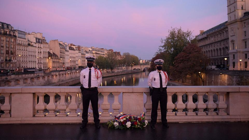 Police officers stand near a wreath of flowers on the Saint Michel bridge during a ceremony to commemorate the brutal repression of an October 17, 1961 demonstration during which at least 120 Algerians were killed during a protest to support Algerian independence, in Paris on October 17, 2021
