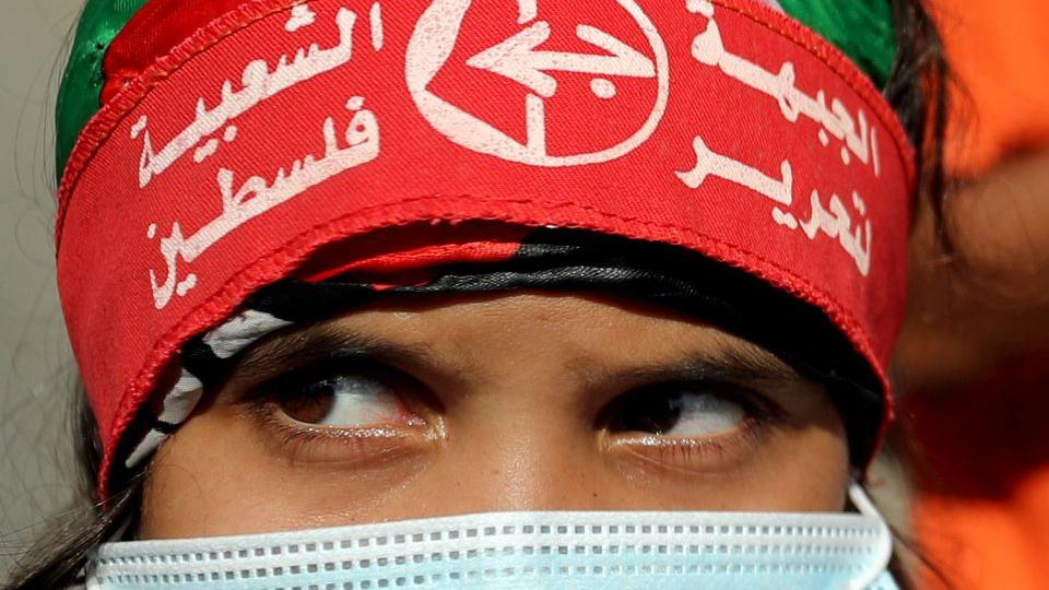 Girl wearing a protective face mask and the headband of the Popular Front for the Liberation of Palestine (PFLP) looks on during a rally to show solidarity with Palestinian prisoners, in Gaza City October 12, 2020.