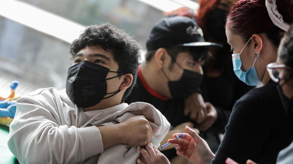 A young man receives a dose of the Pfizer-BioNTech coronavirus vaccine during a vaccination programme in Mexico City, Mexico on October 25, 2021.