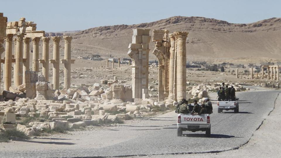 File photo shows Syrian regime forces driving past the Arch of Triumph in the historic city of Palmyra in Syria.