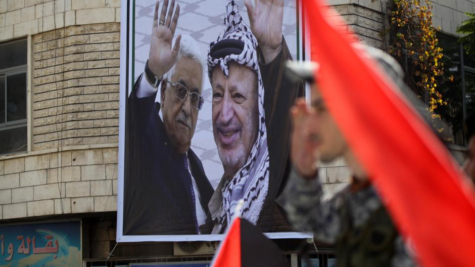 A picture of Palestinian President Mahmoud Abbas and Palestinian former president Yasser Arafat waving together is hung on a wall of a building to mark the 29th anniversary of Palestinian Declaration of Independence in Hebron, West Bank on November 14, 2017.