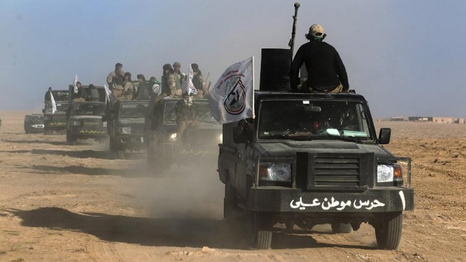 Iraqi forces, supported by members of the Hashed al-Shaabi (Popular Mobilisation units), advance through the Salaheddin province in the western desert bordering Syria after leaving the town of Baiji, on November 24, 2017, as they attempt to flush out remaining Daesh militants in the Al-Jazeera region.
