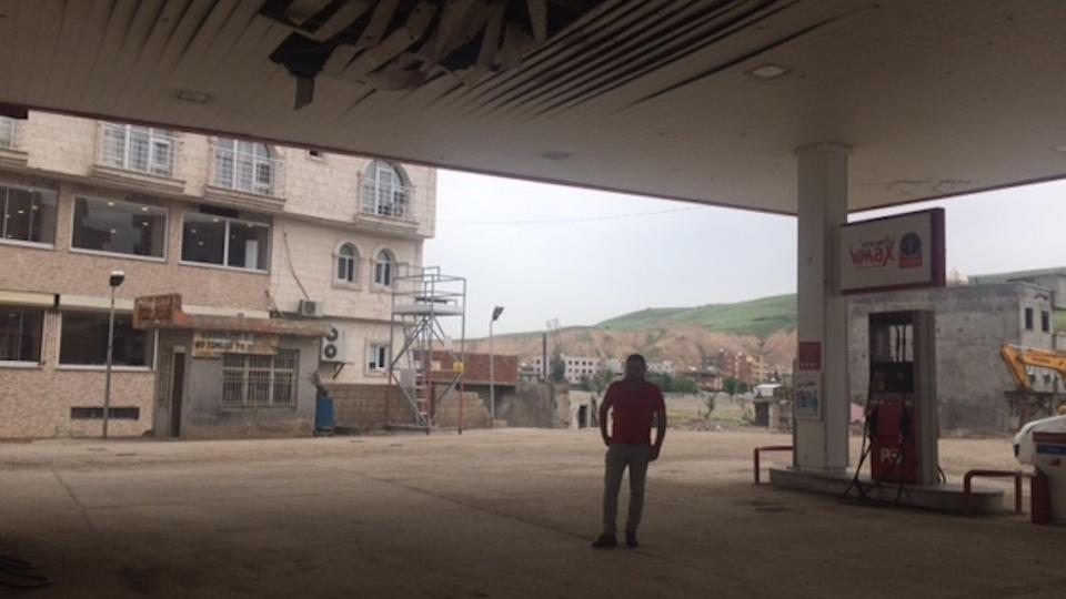 Kalkan stands under the damaged roof of his gas station in Cizre. During the PKK's urban armed campaign in Cizre back in 2015, Kalkan and his friends left the city. When he returned to the city, he saw his gas station was hit. But he was lucky because only the roof was hit.