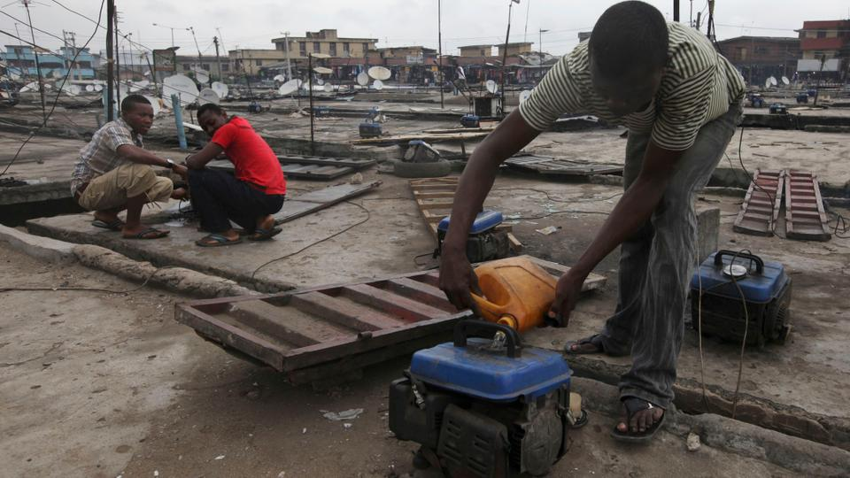 A man refuels a small generator on a store rooftop at Oshodi Market in Lagos, Nigeria. The country is Africa's top oil and gas producer, but it also has chronic power shortages that affect millions of people.