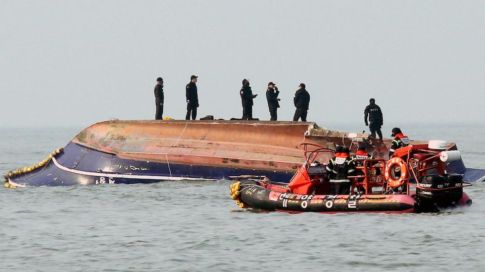 South Korean coastguard members search for missing people after a fishing boat crashed with a fuel tanker at sea near the western port city of Incheon on December 3, 2017.