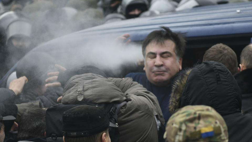 Georgian former President Mikheil Saakashvili struggles out of a police car in Kiev, freed by his supporters after police arrested him.