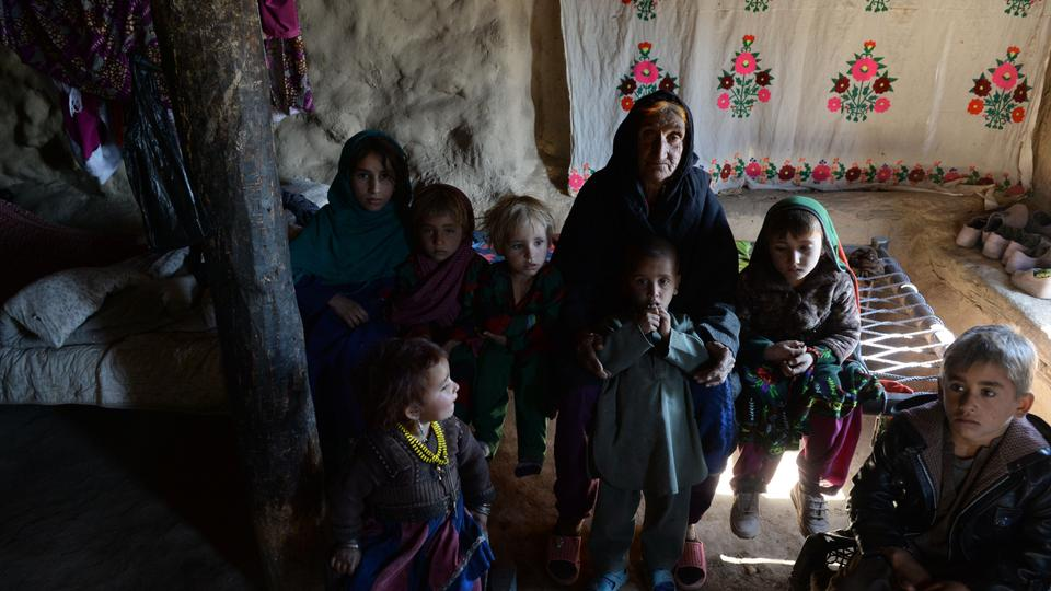 In this photograph taken on October 25, 2017 Afghan widow Janat Bibi, 65, stands with her grandsons inside her muddy house in the remote village of Shemol in the eastern province of Nangarhar.