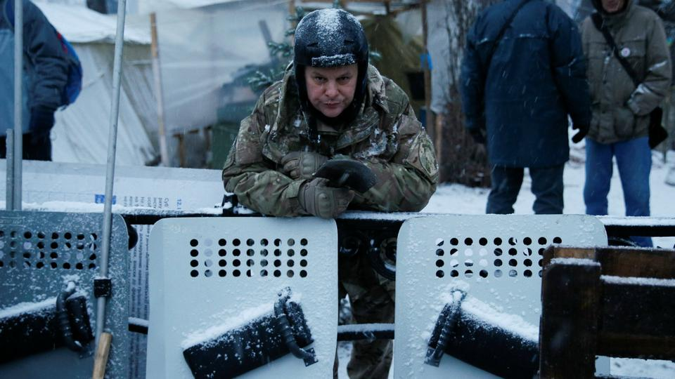 An anti-government protester stands behind a barricade next to the Parliament building in Kiev.