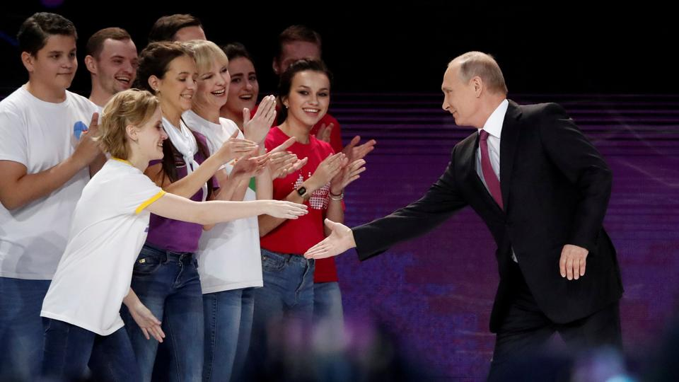 Russian President Vladimir Putin (R) greets participants as he arrives at the congress of volunteers in Moscow, Russia, December 6, 2017.