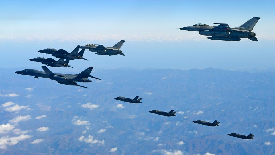 This handout taken and released by the South Korean Defence Ministry in Seoul on December 6, 2017 shows a US Air Force B-1B Lancer bomber (C), two US F-35A and two US F-35B stealth jets (top) flying over South Korea with South Korea's two F-16 and two F-15K fighter jets (bottom) during a joint military drill.