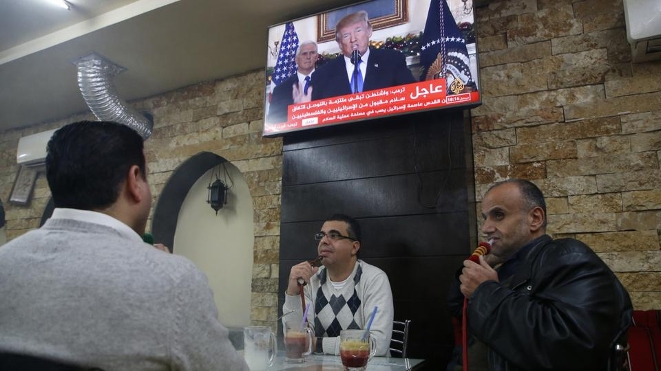 Palestinians sit in a cafe in the West Bank city of Ramallah on December 6, 2017, as TV screens show US President Donald Trump giving a speech in which he announced the recognition of the disputed city of Jerusalem as Israel's capital.