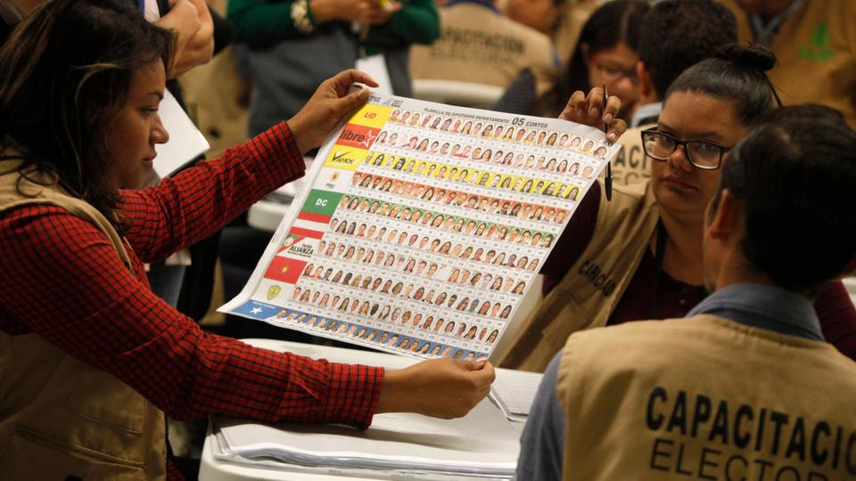 Election workers look at a ballot during a partial recount of presidential and congressional elections in Tegucigalpa, Honduras, Tuesday, Dec. 5, 2017. The head of the election tribunal has not declared a winner for the Nov. 26 presidential elections.