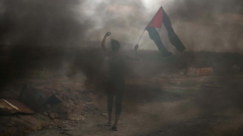 A protester holds a Palestinian flag during clashes with Israeli troops at a protest against US President Donald Trump's decision to recognize Jerusalem as the capital of Israel, near the border with Israel in the southern Gaza Strip December 7, 2017.