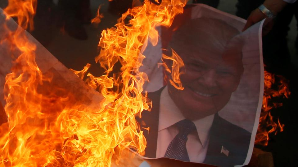 A Palestinian protester burns a poster of US President Donald Trump in Gaza after a US decision to recognise Jerusalem as the capital of Israel on December 7, 2017.