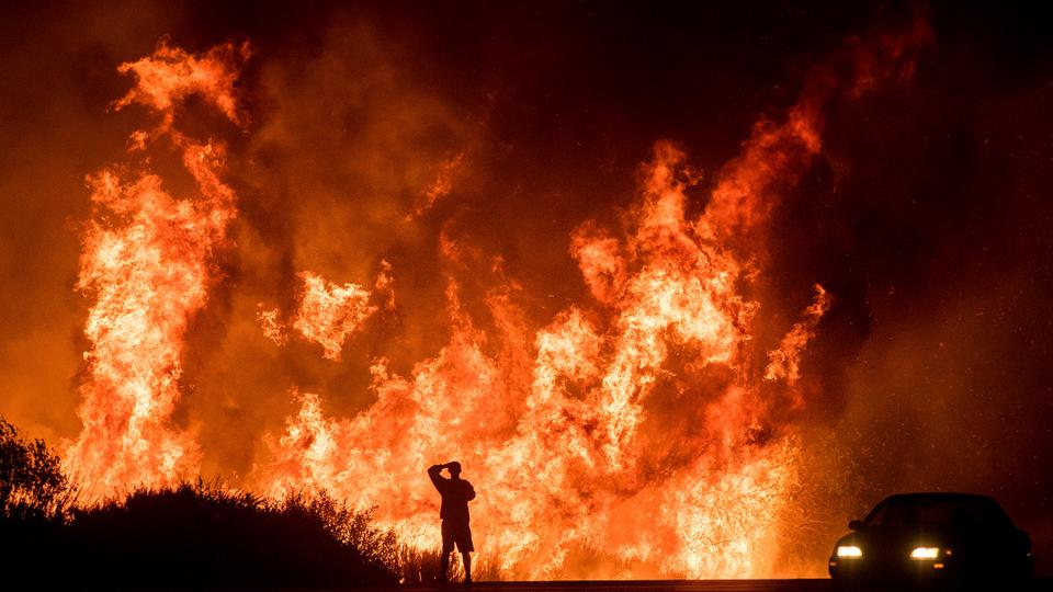 A motorist on Highway 101 watches flames from the Thomas fire leap above the roadway north of Ventura, California.
