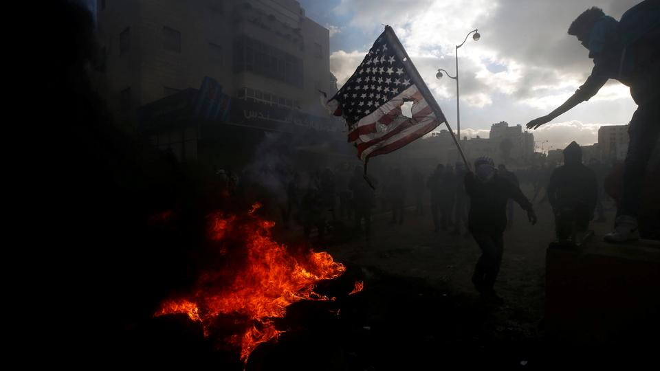 A Palestinian protester prepares to burn a US flag during clashes with Israeli troops at a protest against US President Donald Trump's decision to recognize Jerusalem as the capital of Israel, near the Jewish settlement of Beit El, near the West Bank city of Ramallah on December 7, 2017.