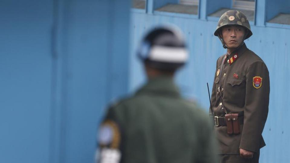 A North Korean soldier stands guard at DMZ in khaki uniform that nod towards a bygone Soviet era.