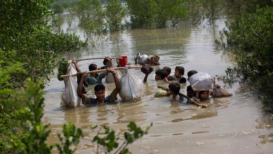 A Rohingya family leaves Myanmar, crossing the Naf river on the border with Bangladesh.