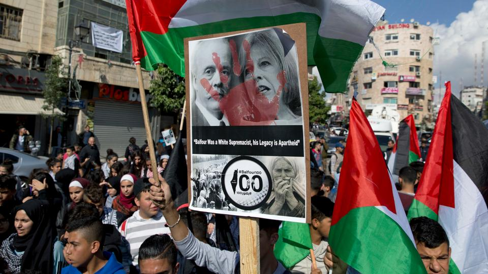 Palestinian protesters wave flags and carry a defaced photo of  Arthur Balfour on the 100th anniversary of the Balfour Declaration, in Ramallah, West Bank on Nov. 2, 2017. Balfour, a prominent British diplomat, was instrumental in creating Zionism inspired Jewish homeland of what is now Israel.