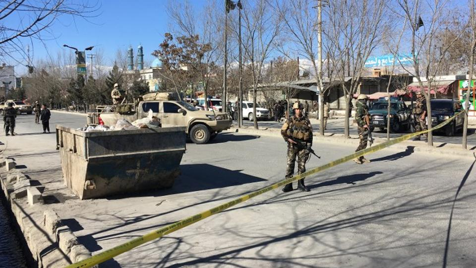 Afghan security forces stand guard near the site of multiple blasts in Kabul on December 28, 2017.