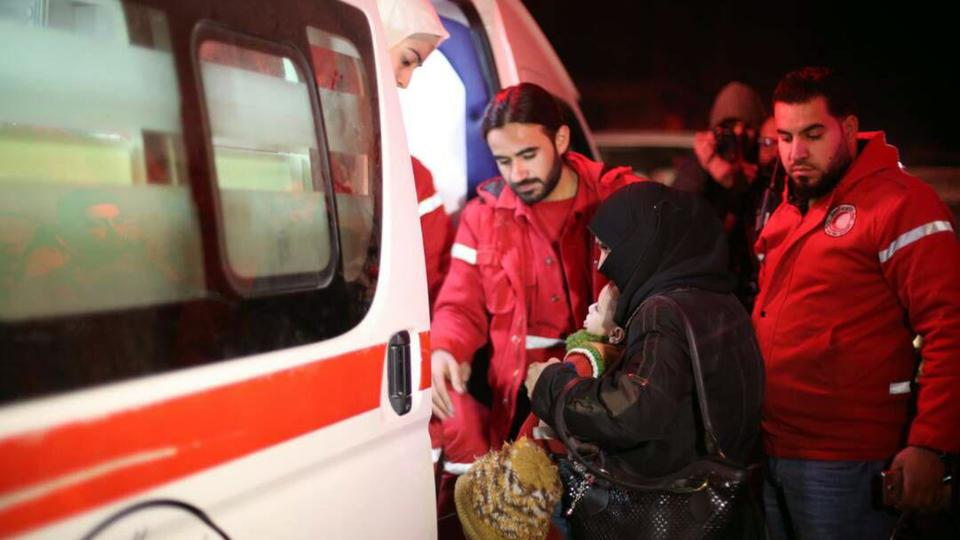 Syrian Arab Red Crescent help a woman carrying a baby board an ambulance during the evacuation of sick people from Eastern Ghouta, near Damascus, Syria, Wednesday, December 27, 2017.