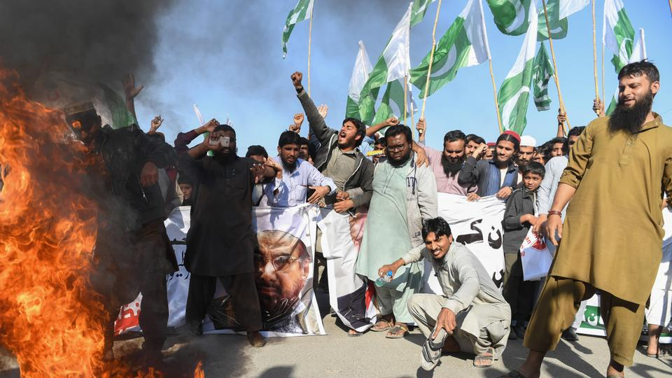Activists of the Difa e Pakistan Council shout anti-US slogans and burn an American flag at a protest in Karachi on January 2, 2018.