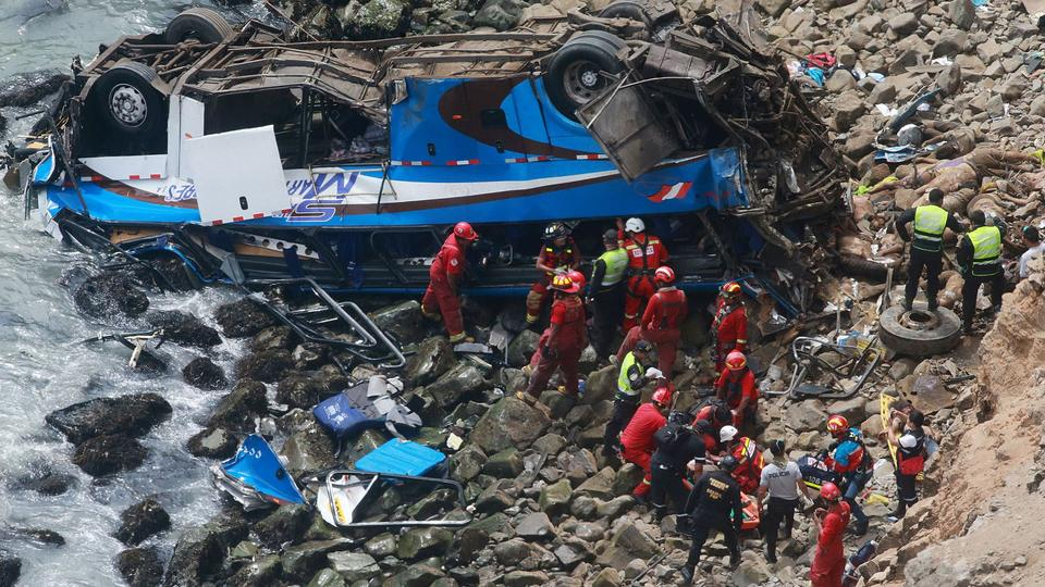 Rescuers, police and firefighters at the scene after a bus plunged around 100 metres over a cliff after colliding with a truck on a coastal highway near Pasamayo, Peru, January 2, 2018.