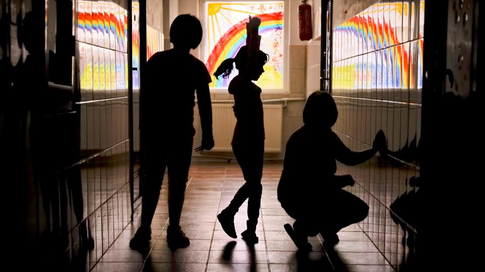 This November 3, 2017 file photo shows children at the Robin Hood orphanage trying a ballet move while posing for a photo in a corridor with painted windows, in Bucharest, Romania.