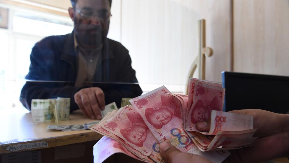 A Pakistani currency dealer counts Chinese currency for his customer at his shop in Quetta on January 3, 2018.