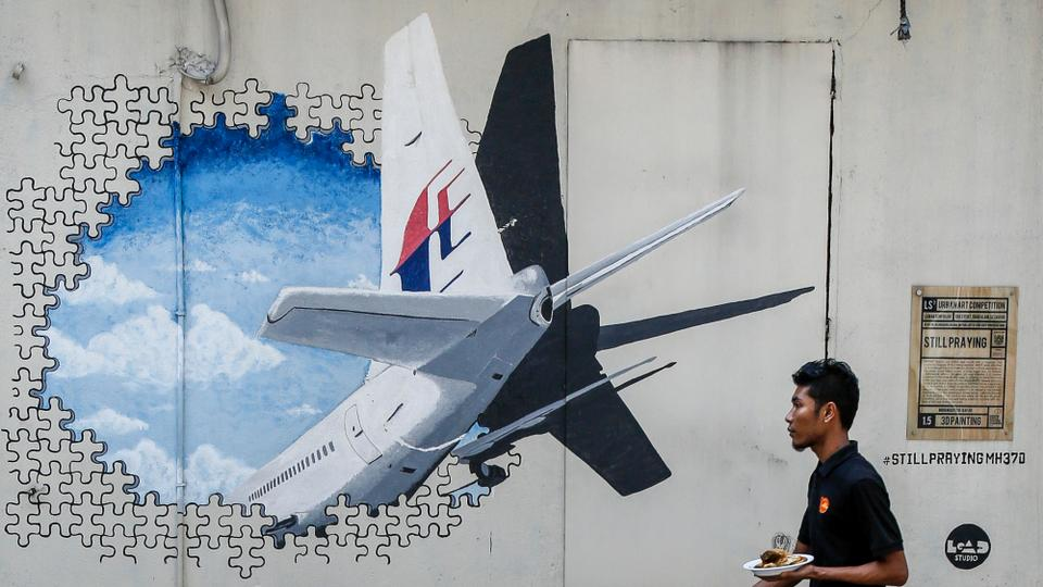 A waiter walks past a mural of flight MH370 in Shah Alam outside Kuala Lumpur, Malaysia in this February 23, 2016 file photo.