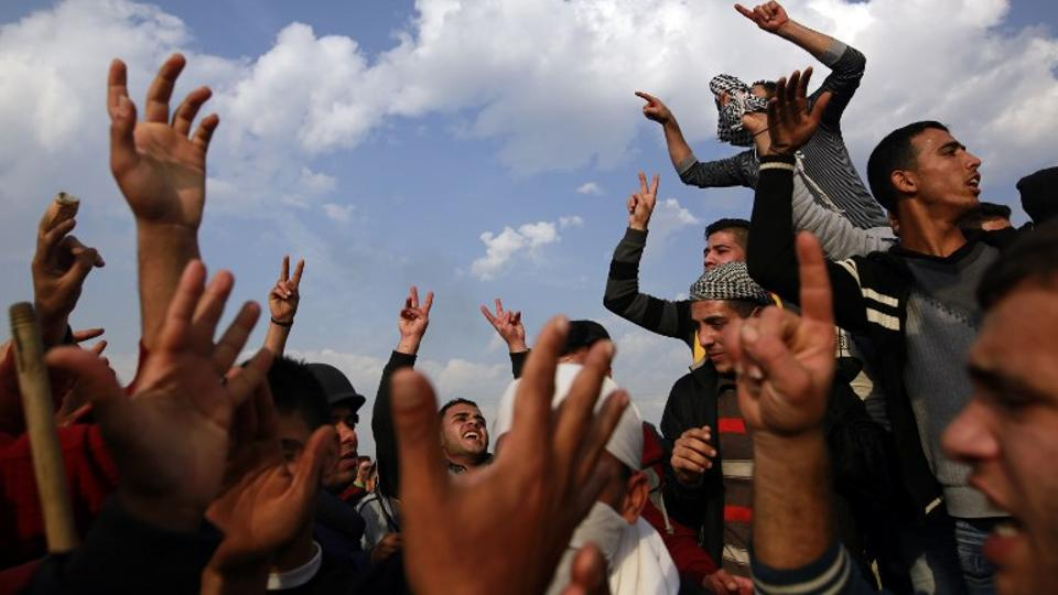 Palestinian protesters chant slogans during a demonstration near the border fence east of Gaza City on December 29, 2017.