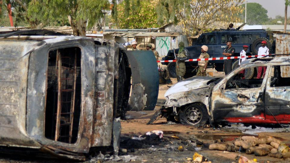 Police officers stand guard following a suicide bomb explosion at a bus station in Nigeria (file photo).