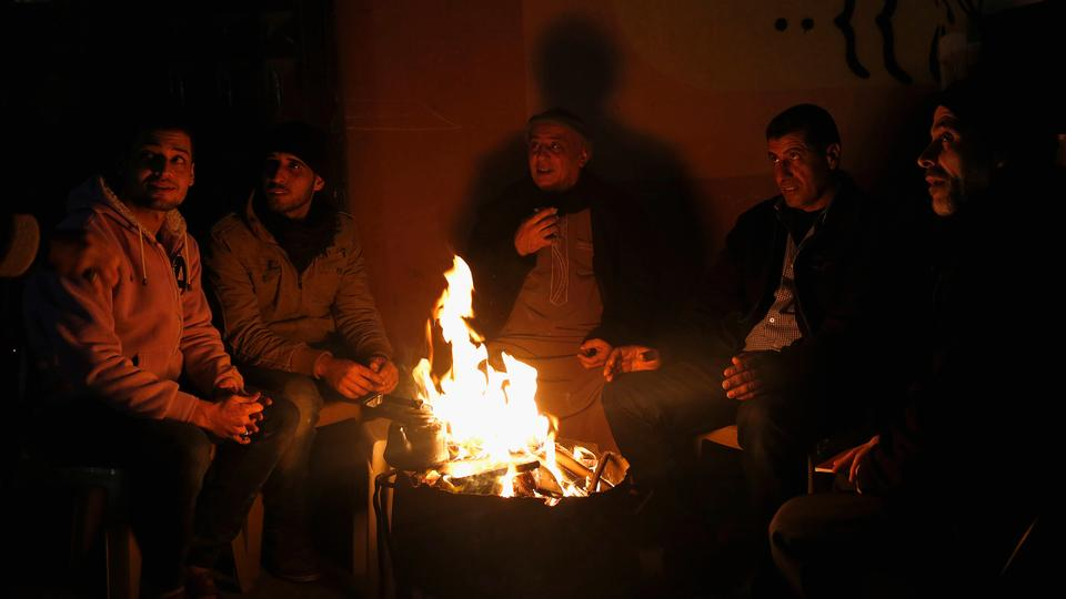 Palestinians sit around wood set alight in a fireplace outside their home during a power outage in Gaza City (file photo).