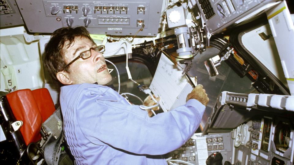 John W. Young, STS-1 mission Commander, prepares to log flight-pertinent data in a loose-leaf flight activities notebook onboard the Space Shuttle Columbia on April 14, 1981.