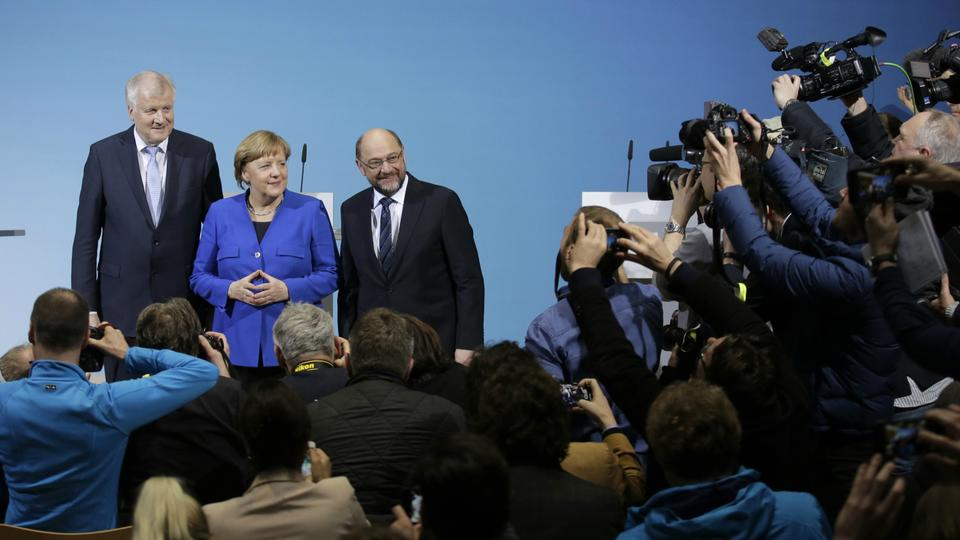 German Chancellor Angela Merkel is flanked by Bavarian governor Horst Seehofer, left, and Social Democratic Party Chairman Martin Schulz as they pose for a photo after the exploratory talks between Merkel's Christian Democratic block and the Social Democrats on forming a new German government in Berlin.