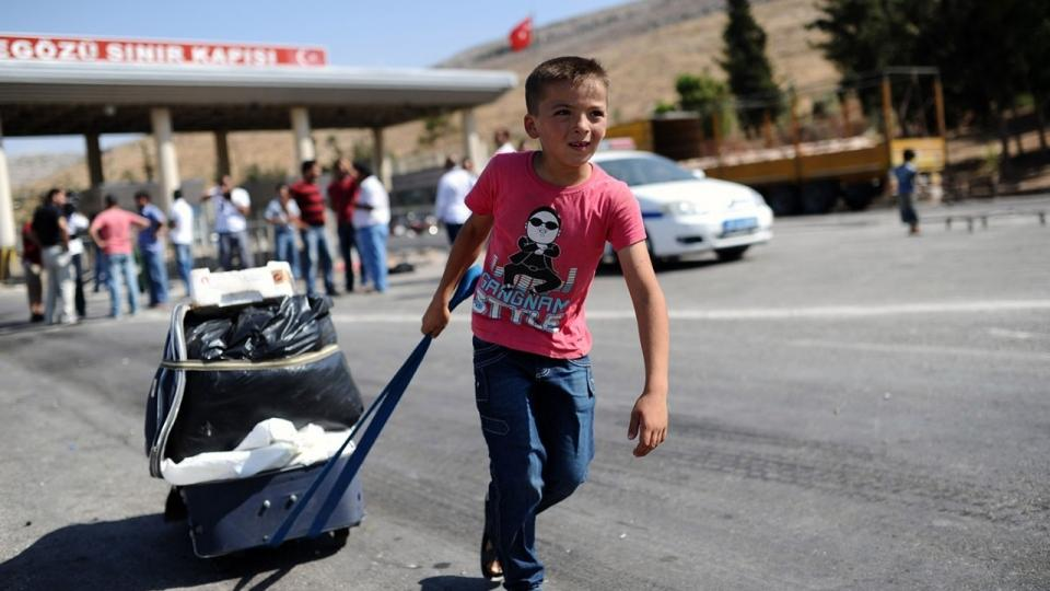 A Syrian refugee child enters Turkey from border, carrying his belongings on January 14, 2016.