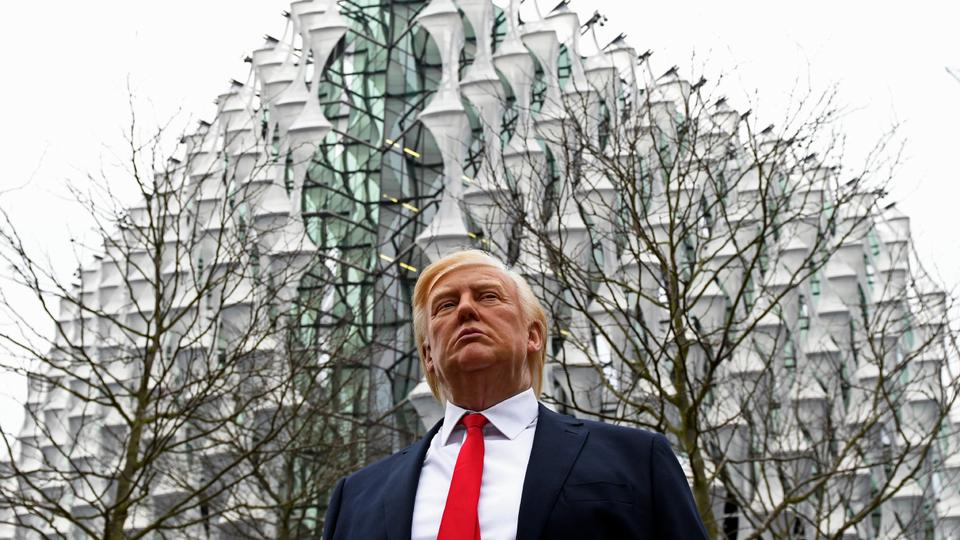 A Madame Tussauds wax figure of US President Donald Trump stands outside the new US Embassy in Embassy Gardens in south-west London on January 12, 2018. US President Donald Trump said today he no longer plans to attend the opening of the new US embassy in London. He announced the decision in a midnight tweet amid reports in Britain that a Trump visit would be met with protests.