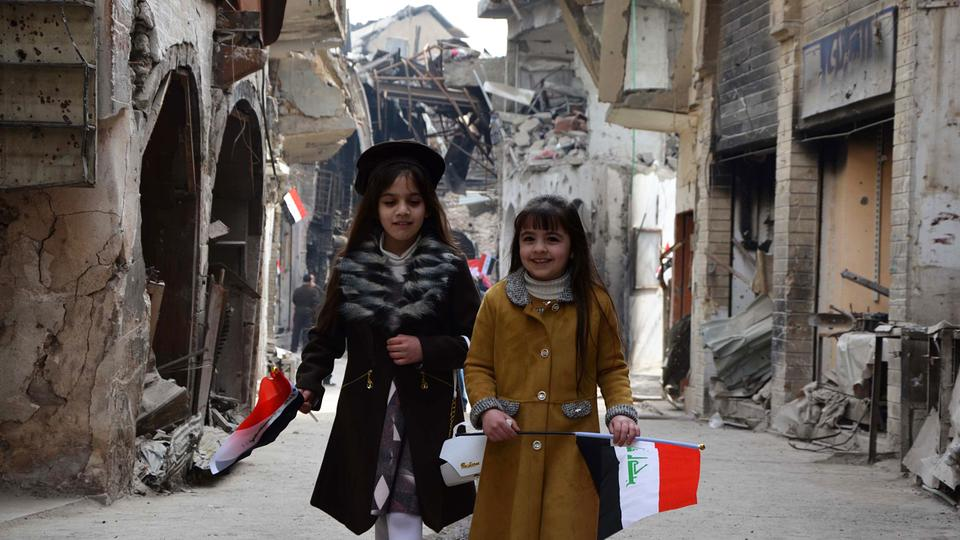 Iraqi girls walk holding their national flag towards a ceremony for the re-opening of the Bab al-Saray market in the old city of Mosul on January 11, 2018.
