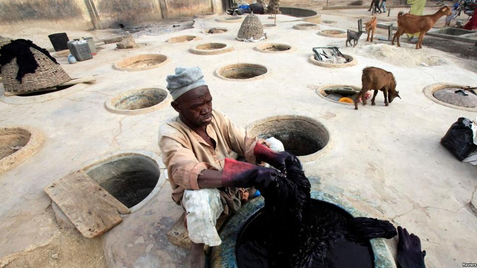 A man dyes fabrics in traditional styles in Kano, Nigeria.
