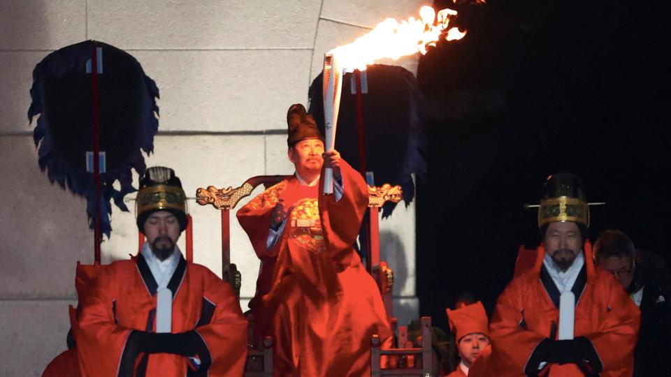 A torchbearer wearing a traditional costume carries the Olympic torch in Seoul, South Korea on January 13, 2018.