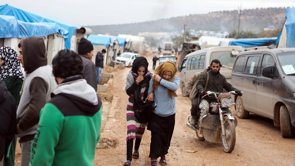 Syrians, evacuated from Aleppo, walk in a refugee camp near Idlib, Syria, Friday, Dec. 16, 2016.