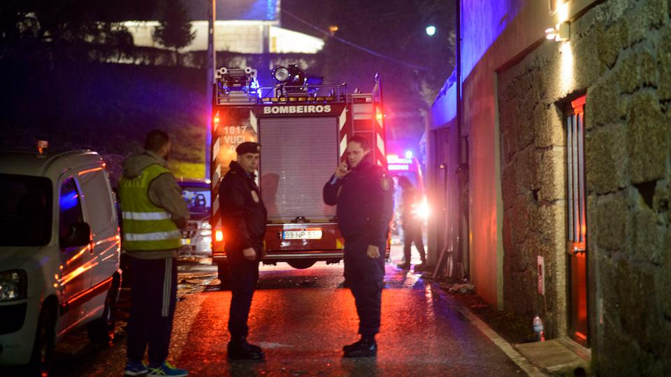Policemen stand outside the building, at right, where a heater exploded killing people in the village of Vila Nova da Rainha, outside Tondela, northern Portugal, in the early hours of Sunday, Jan. 14 2018.