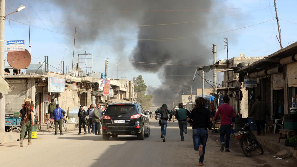 People rush to the site of an airstrike on the Syrian city of Saraqib, southwest of Aleppo, on January 10, 2018.