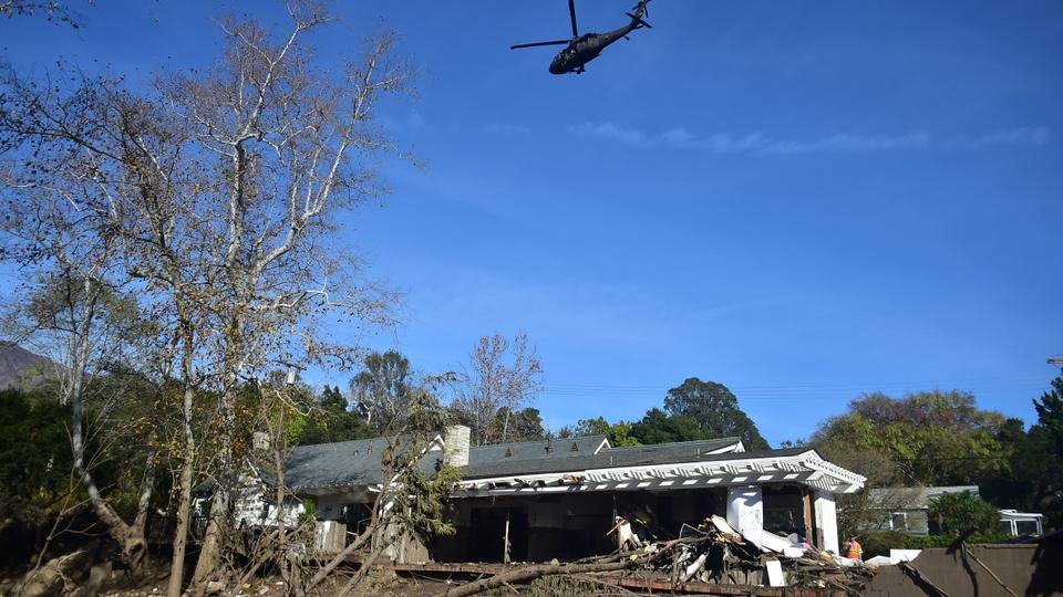 A helicopter flies over a home damaged in a mud slide in Montecito, California January 12, 2018.
