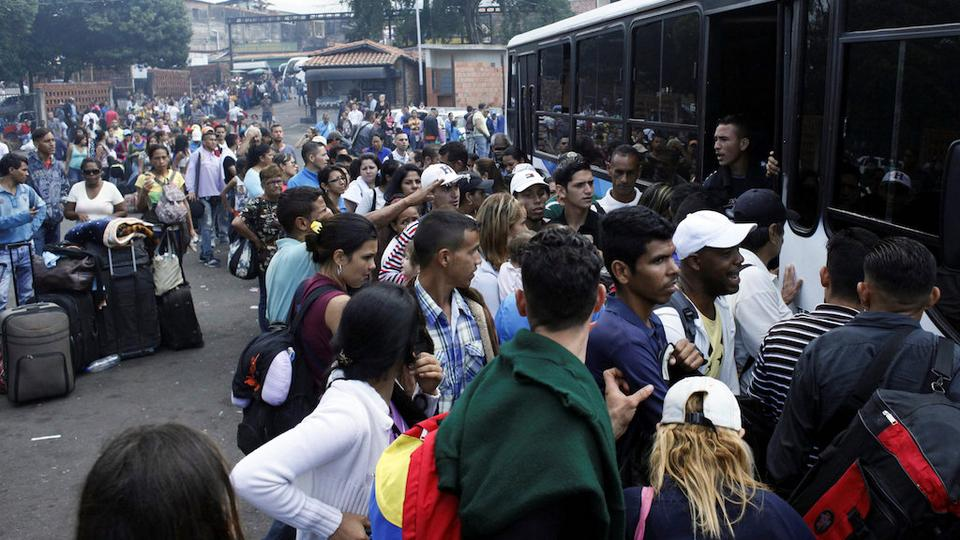 People queue to try to find a spot on a bus to travel to the city of San Antonio near the Colombian border at the bus station in San Cristobal, Venezuela December 14, 2017.
