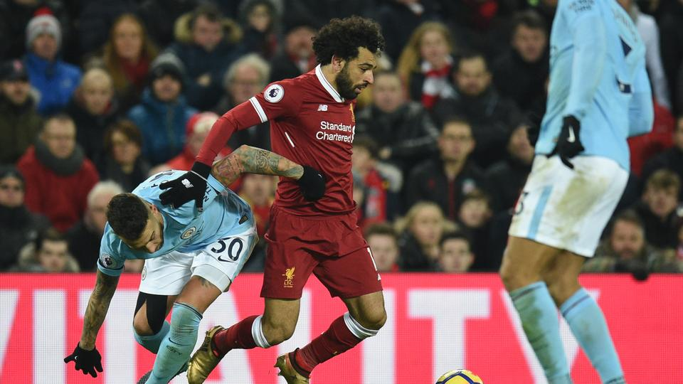 Liverpool's Egyptian midfielder Mohamed Salah (C) tangles with Manchester City's Argentinian defender Nicolas Otamendi (L) during the English Premier League football match between Liverpool and Manchester City at Anfield in Liverpool, north west England on January 14, 2018.